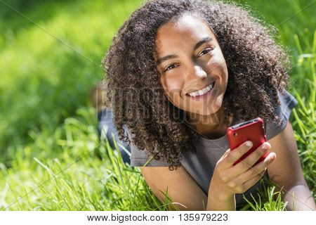 Outdoor portrait of beautiful happy mixed race African American girl teenager female young woman smiling with perfect teeth texting on cell phone