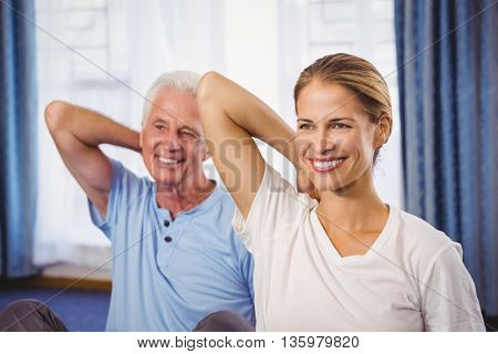 Fitness instructor and senior doing exercises during fitness class