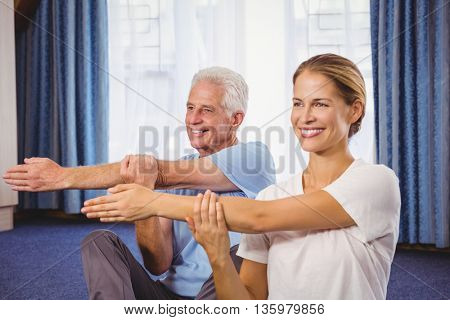 Portrait of fitness instructor and senior stretching their arms during fitness class