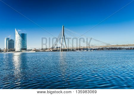 A view of the buildings and Vansu bridge on the banks of the Daugava River in Riga, Latvia at winter