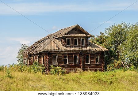Old destroyed log wooden house in russian village Vologda region. Sunny summer day