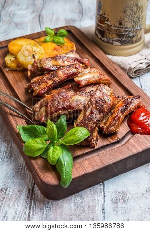 elicious Grilled Pork Rib and Fried Potato Wedges with Sauce on wooden cutting board, white wooden background