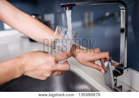 Cropped hand of woman filling water in glass from faucet at kitchen sink