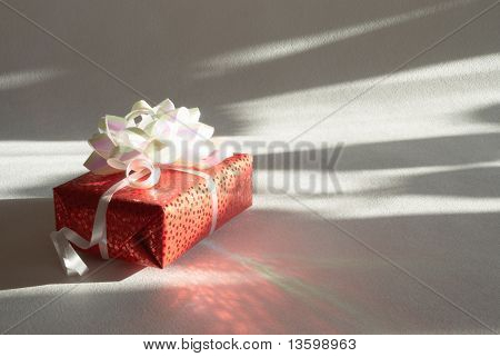 Gift In A Red Paper On A Light Background