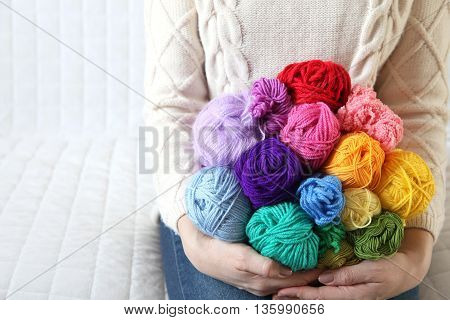Woman sitting on the couch and holding a colored yarn. Knitted sweater. White background. Knitter.