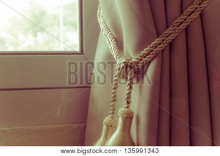 Curtains tassel with rope by the window on the left vintage retro style.