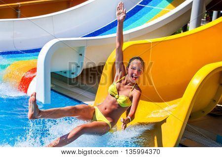 Child on water slide at aquapark show thumb up. There are some water slides with flowing water in aqua park. Summer water park holiday. Outdoor.
