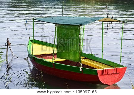 Closeup of a floating colorful rowboat anchored on the pier