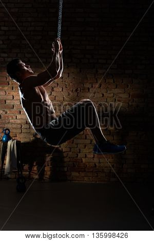 Artistic photo of muscular man doing crossfit workout with chain, indoors.