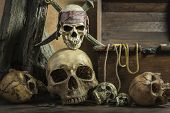 closeup pirate skull with two swords over on human skull pile awesome and treasure coffer background still life style pirate concept for halloween poster