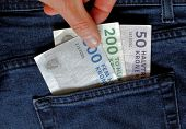 Hand taking Danish bank notes from a jeans pocket poster