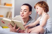 I like this tale. Relaxed contended woman reading a bedtime story for her funny little son poster