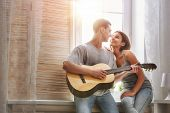 Happy couple in love. Stunning sensual portrait of young stylish fashion couple indoors. Young man playing guitar for his beloved girl. poster