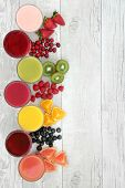 Healthy fresh fruit and juice smoothie drinks over distressed white wood background, high in antioxidants, vitamins, anthocyanins, dietary fiber and minerals. poster