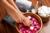 Closeup photo of a female feet at spa salon on pedicure procedure. Female legs in water decoration the flowers. poster