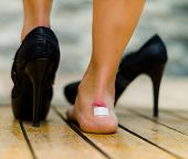 High heels hurts very often, feet with white little patch on ankle, one feet on the floor and other with black shoe. poster