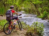 Bikes cycling girl. Girl with big rucksack rides bicycle. Girl cycling fording throught water . Cycling trip is good for health. Cyclist is looking throught river. poster