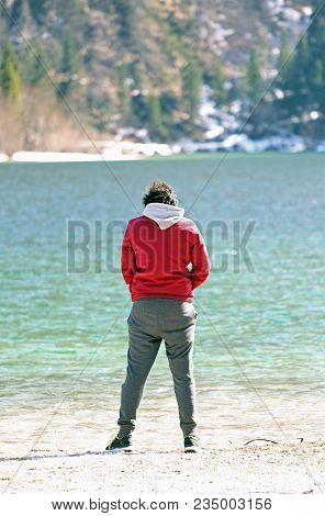 Young Teenager While Peeing On The Waters Of The Alpine Pond