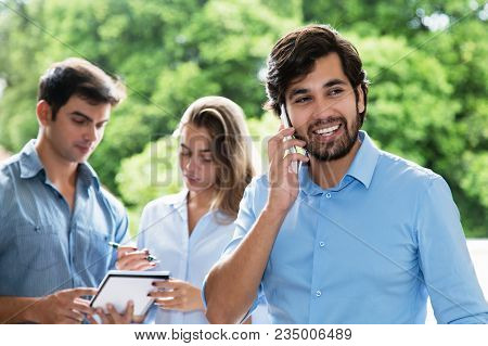 Laughing Latin American Businessman At Phone Outdoors With Other Smart Businesspeople