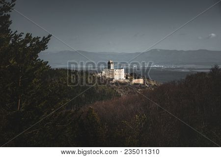 Photo Of Illuminated Castle With Wall On Right Side In Slovakia - Europe (podhradie). Image Of Ruins