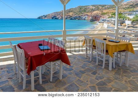 Tables And Chairs In Typical Greek Tavern With View Of Aegean Sea. Milso Island, Greece