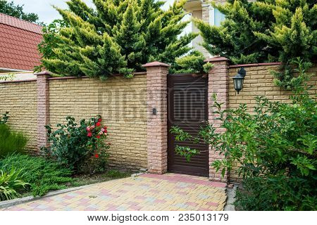Entrance House Group With A Wicket And Stone Fence Surrounded By Green Bushes And Trees, Horizontal