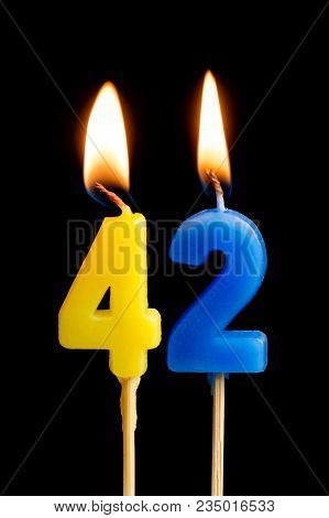 Burning Candles In The Form Of 42 Forty Two (numbers, Dates) For Cake Isolated On Black Background.