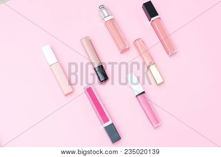 Women's Lip Gloss Set For Make-up On A Pink Background. Geometric Style