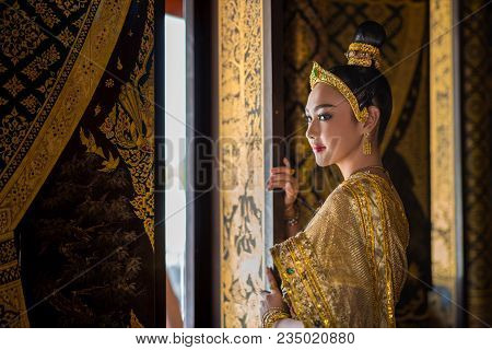 Beautiful Asia Woman In Gorgeous Antique Thai Dress Stand Near Ancient Gold Threads Old Thai Pattern