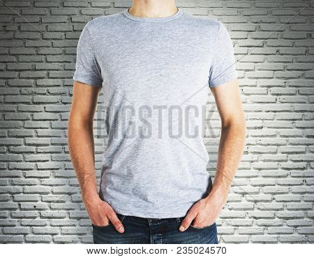 Man Wearing Blank Grey Shirt On Brick Wall Background. Advertisement And Design Concept. Mock Up