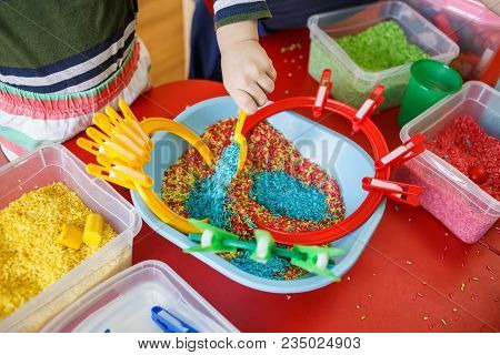 Toddlers Playing With Sensory Bin With Colourful Rice On Red Table.