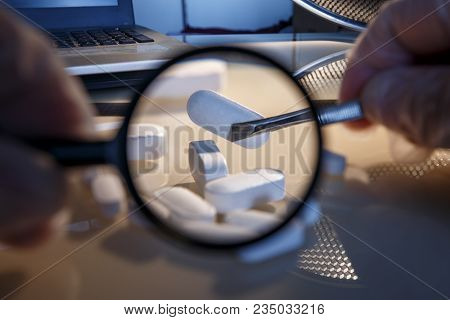 Tablets And A Magnifying Glass As A Concept For Investigating Counterfeit In The Medical Industry. Q