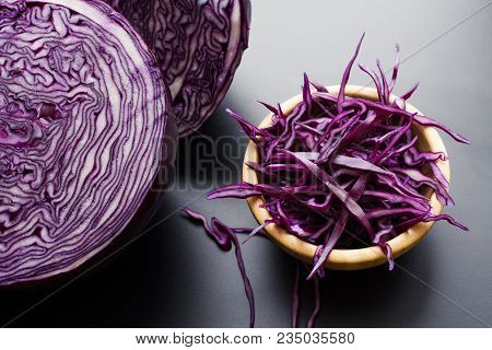 Chopped Red Cabbage Salad In Wooden Bowl With A Half Of Cabbage Head Over Dark Gray Background