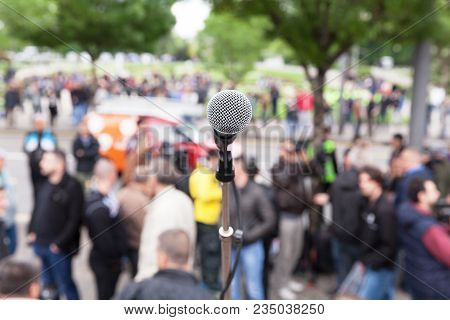 Street Protest. Public Demonstration. Microphone In Focus Against Blurred Audience.