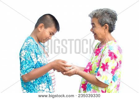 Boy Holding Bowl Of Water And Flower Pour Down To Old Hands Woman On White Background , Respect Conc
