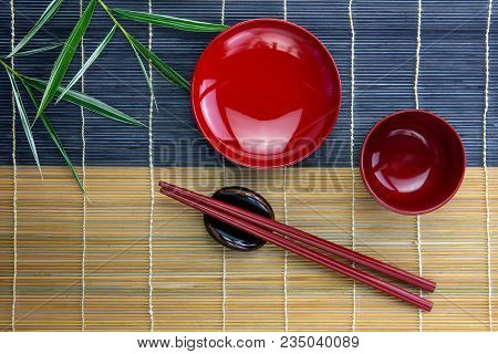 Empty Red Bowls With Red Chopsticks On Holder And Bamboo Leaves Placed On Bamboo Mat, Top View Or Fl