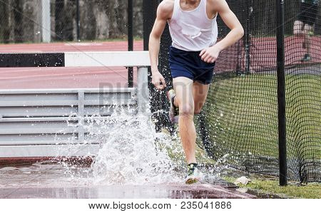 A Runner Splashes At The End Of The Steeplechase Water Pit During A High School Track Race.
