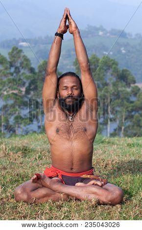 Indian Man Meditating In Lotus Yoga Pose On Green Grass In Kerala, India