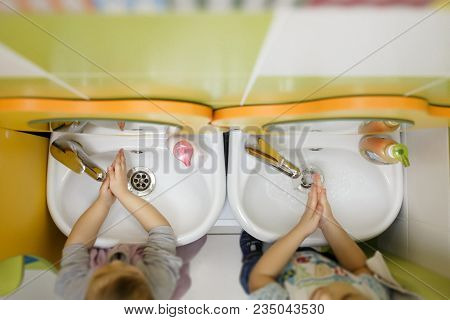 Two Children Washing Hands In A White Basin With A Bar Of Soap. Kindergarten Or Nursery Washing Room