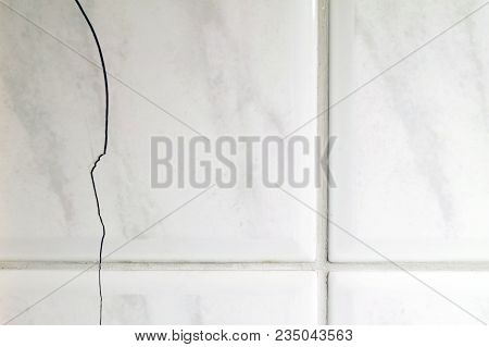 Cracked Tiles On The Bathroom Wall Need Repair. Possible Sign Of Water Damage. Horizontal Image Of B