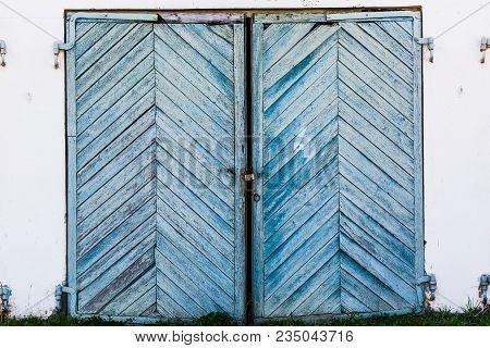 Old, Blue, Skewed Garage Doors On A Collapsing Brick Wall.