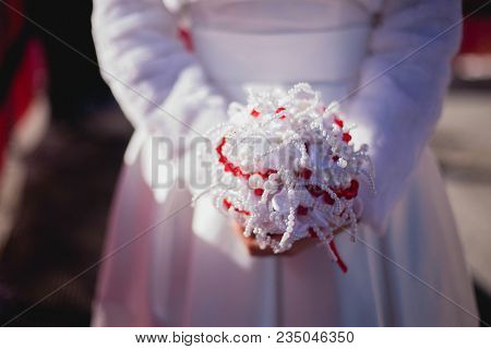 Closeup Of Winter Bride Hands Holding Wedding Bouquet. Wedding Bouquet Made From Pearls And Red Bead