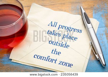 All progress takes place outside the comfort zone - inspiraitonal handwriting on a napkin with a cup of tea