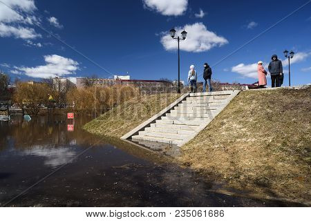Orel, Russia, April 07, 2018: Flood In Town. People Walking Along Flooded Embankment With Cloudy Sky