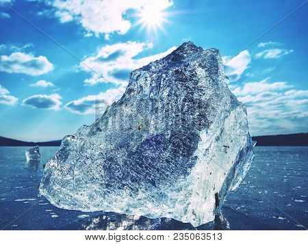 Sharp Piece Of Ice. A Symbol Of Harsh Winter. The Rays Of The Sun Form Rainbow Shadows In The Cracks