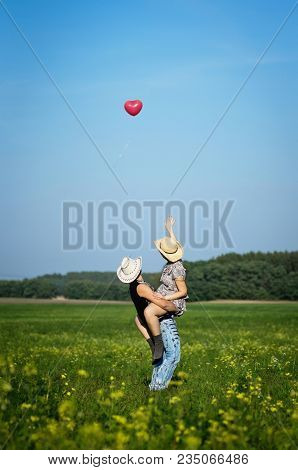 Beautiful Happy Young Couple Have Fun In Summer Sunny Field Together. People Wear Cowboy Hats. Cowgi