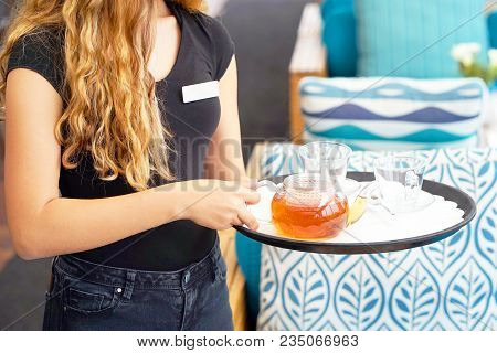 A Waitress Is Carrying Tea. Hospitable Girl Waitress Holding Tray With Cup Of Tea And Tea Glass Teap