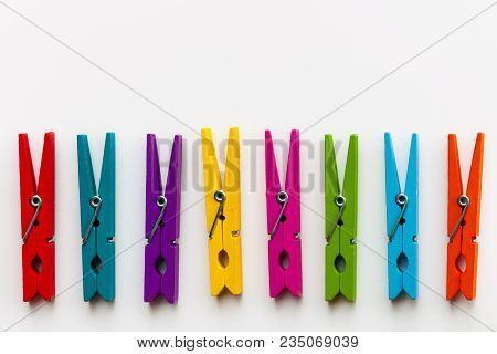 Colorful Wooden Clothespins On White Background With Copy Space/diversity Concept