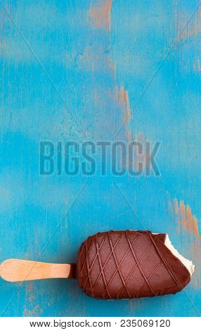 Vanilla Ice Cream Bar With Chocolate Coating On Rustic Blue Wooden Background With Copy Space