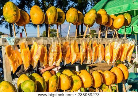 Whole Ripe Yellow Mangoes On Sticks & Sliced Ripe Mangoes In Bags On Street Stall, Guatemala, Centra